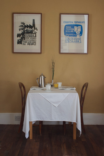 Breakfast Table laid with stainless steel coffee pat, juices and prints on the wall above.